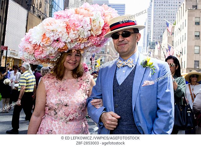 New York, NY - April 16, 2017. A man and a woman New York's annual Easter Bonnet Parade and Festival on Fifth Avenue. The Woman wears a hat that appears to be 3...