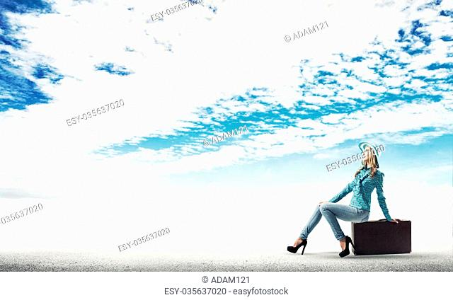 Beautiful woman traveler in hat sitting on her retro suitcase