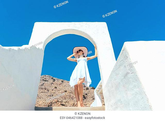 Woman climbing stairs in Greece under a clear blue sky