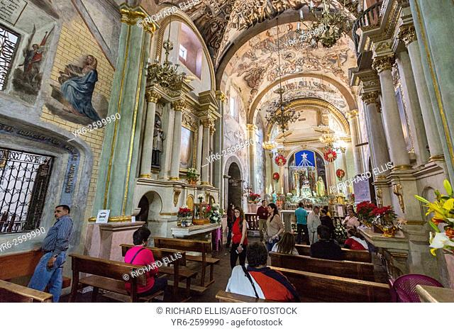 Worshipers inside the Sanctuary of Atotonilco with Mexican folk Baroque murals painted on the ceiling and walls in Atotonilco, Mexico