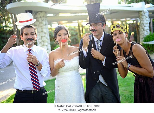 Just married couple playing with costumes and guests in wedding party