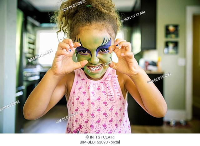 Mixed race girl growling with face paint