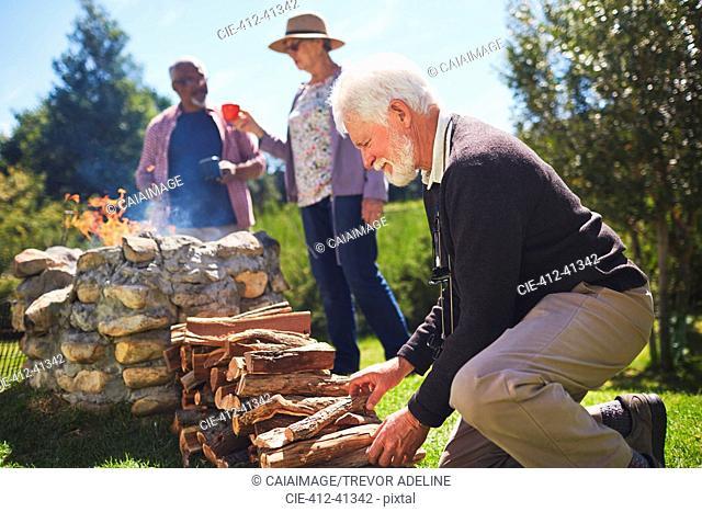 Active senior man stacking firewood
