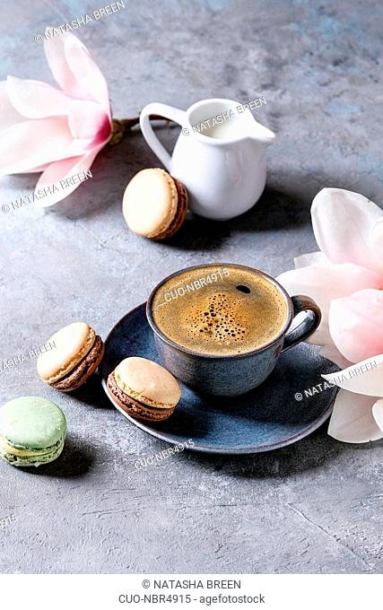 Blue cup of black espresso coffee with french dessert macaroons, cream and spring flowers magnolia branches over grey texture background