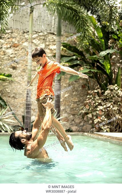 A man standing in a swimming pool lifting a boy up in the air
