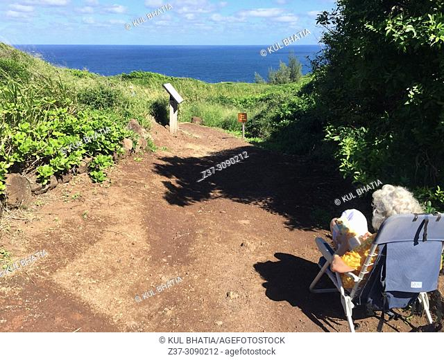 A very elderly woman sitting in a chair at the start of a walking trail, Maui, Hawaii, USA