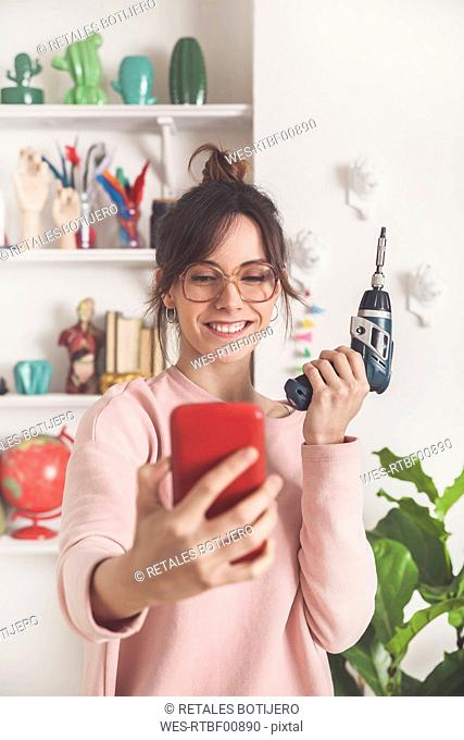 Portrait of smiling young woman taking selfie with electric screwdriver at home