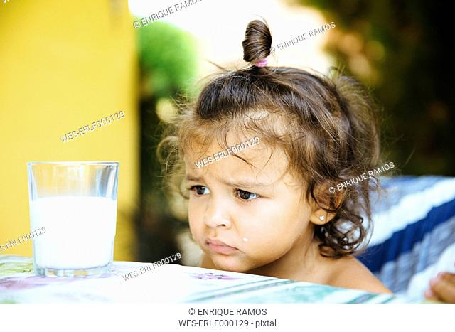 Portrait of unhappy little girl with glass of milk