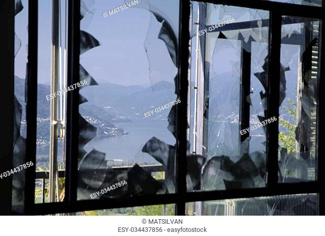 Broken windows with mountain and a lake outside