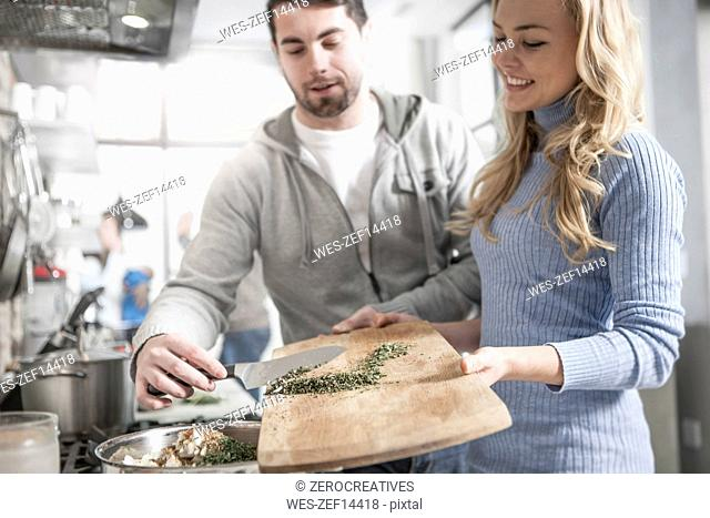 Couple helping one another moving spices in pot