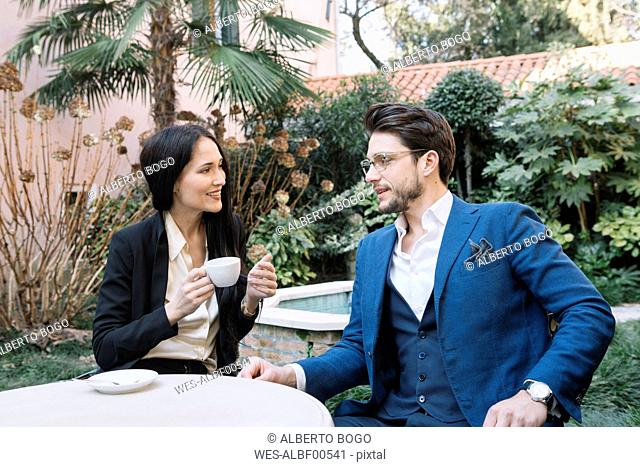 Elegant couple talking in a garden cafe