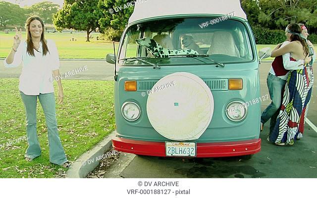 A Dalmatian in a VW Bus watches women outside
