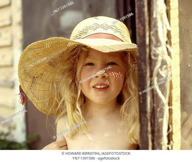 Portrait of a young blond girl in her straw sun bonnet at her back door as the sun sprinkles little highlights on her nose