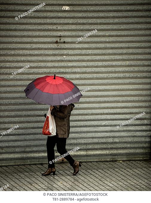People walking in the rain, With umbrella, Madrid, Spain
