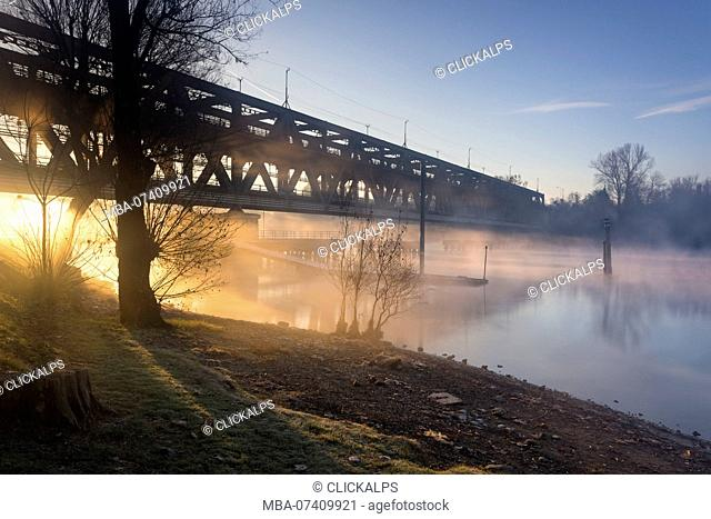 Rays of the light pass through the Ponte di Ferro in a foggy autumnal morning on the shores of river Ticino. Sesto Calende, Lake Maggiore, Varese Province