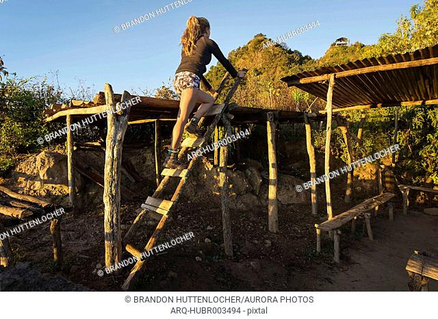 Young woman climbing ladder onto roof of shack in jungle of Guatemala