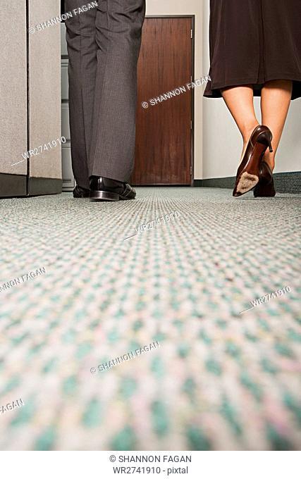 Two colleagues walking along corridor