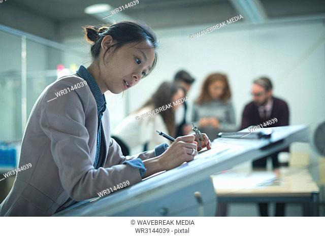 Female executive working over drafting table
