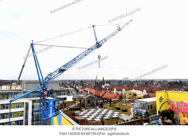 27 March 2019, Bavaria, Munich: A crane erects a bell tower for FLATZ on the roof of the Kistlerhof, where the artist's studio is located