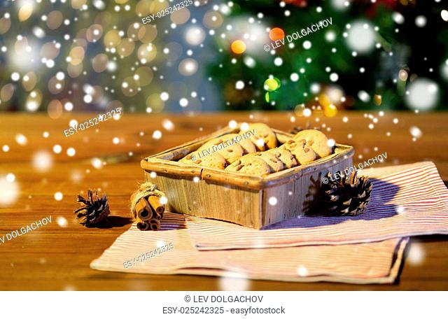 christmas, holidays, food and baking concept - close up of oat cookies in wooden box and cinnamon on table over lights