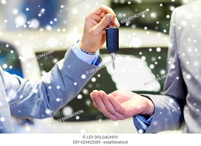 auto business, car sale, deal and people concept - close up of male hands with car key in auto show or salon over snow effect