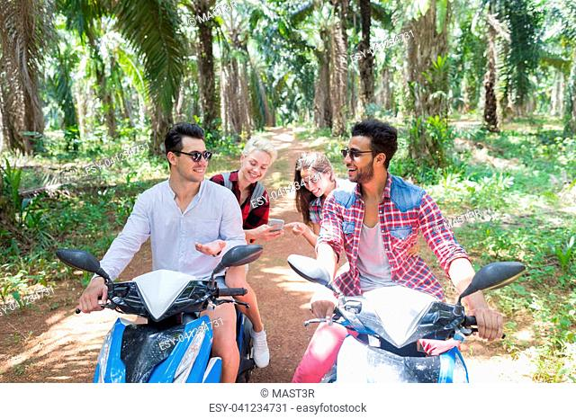 Cheerful Man Talking Sitting On Scooters While Women Watching Photos On Cell Smart Phone Young People Friends Travel On Bikes Together On Road Trip
