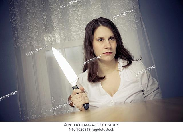 Young woman holding a large knife