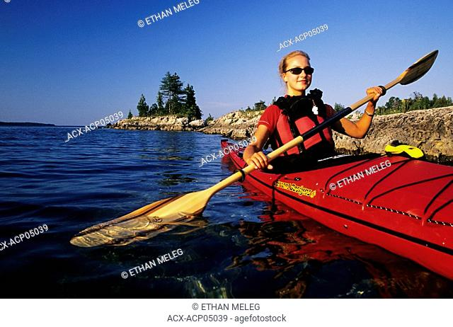 A kayaker paddles on Lake Huron in Fathom Five National Marine Park, Tobermory, Bruce Peninsula, Ontario, Canada