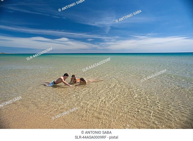 Friends playing in surf on beach