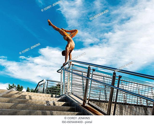 Mature man balancing on railings, South Pointe Park, South Beach, Miami, Florida, USA