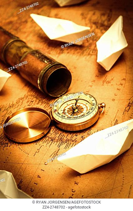 Nautical navigation concept of a old-fashioned compass and telescope placed on old world map with cardboard sailing ships. Maps and bearings