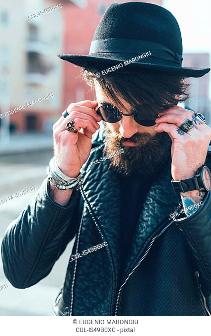 Young male hipster putting on sunglasses in city