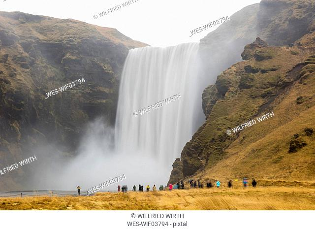 Iceland, tourists at Skogafoss Waterfall