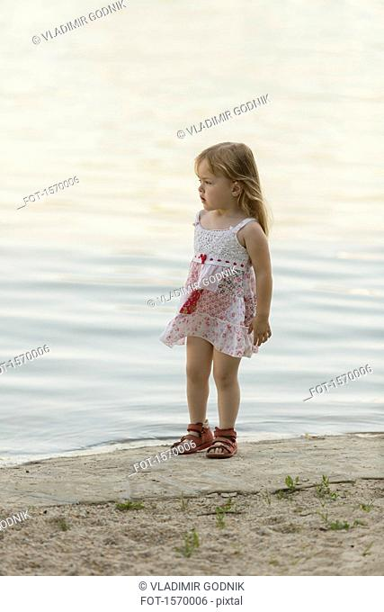 Thoughtful cute girl standing at lakeshore