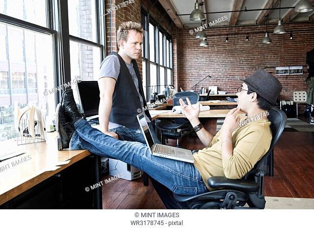 Caucasian man and Hispanic man discussing a problem at a creative office work station