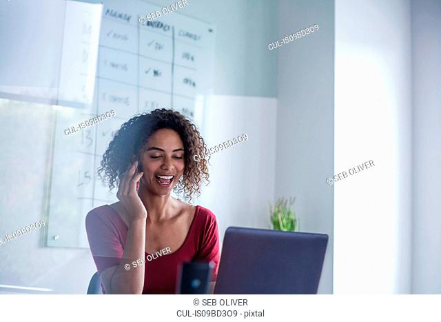 Businesswomen in office making telephone call smiling