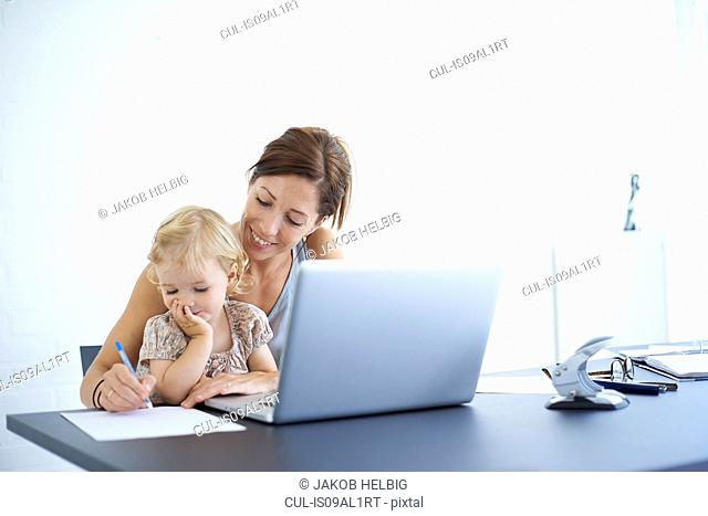Mid adult woman writing notes with toddler daughter on her lap