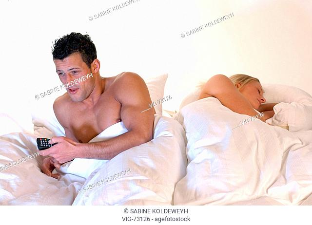 Couple sitting in the bed. The man is watching television. The woman is sleeping. (posed). - 22/08/2004