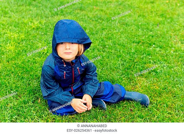 Cute kid resting outdoors, sitting on a lawn, playing on a rainy day, wearing blue waterpoof all-in-one suit