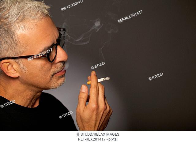 senior man smoking a cigarette cool stylish studio