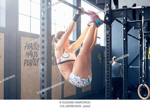 Woman using chin up bar in gym