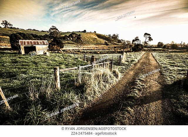 Outback Australia landscape of an old wooden shed in the middle of a field with rural dirt road. Heybridge, Tasmania, Australia