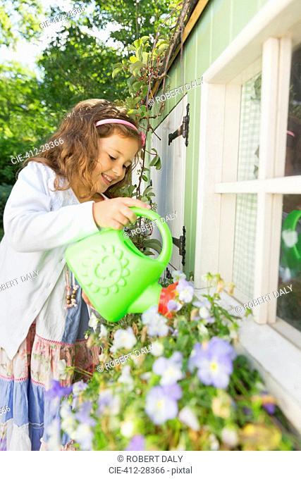 Girl watering flowers in playhouse flower box