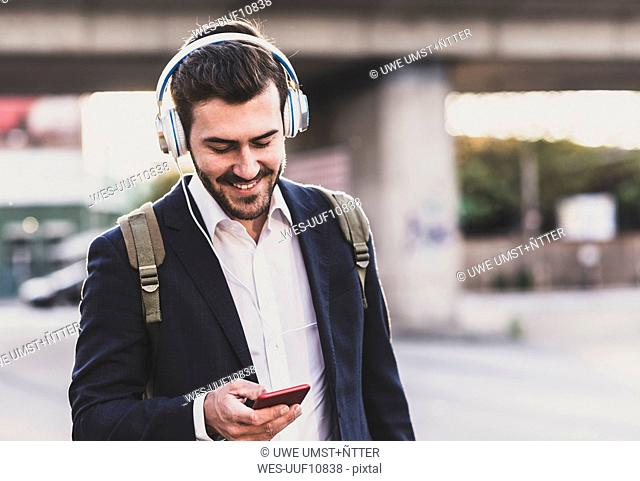 Smiling young man owearing headphones checking cell phone