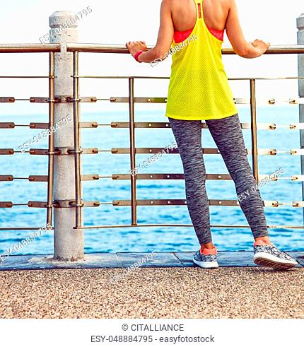 Look Good, Feel great! Closeup on young woman in fitness outfit standing at the embankment