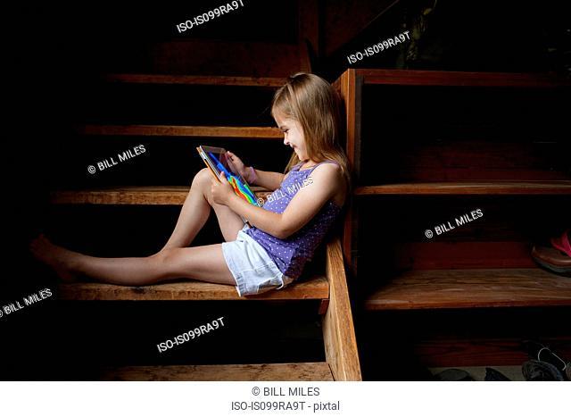 Little girl sitting on basement steps, looking at digital tablet