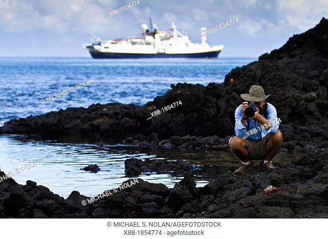 Guest from the Lindblad Expedition ship National Geographic Endeavour photographing in the tide pools on Floreana Island in the Galapagos Islands, Ecuador