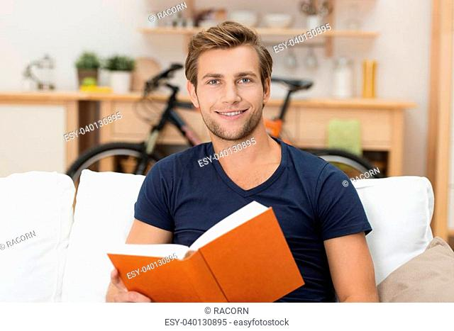 Handsome young man sitting on a sofa at home reading a hardcover book enjoying the story or studying towards his university classes