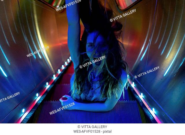 Portrait of blue illuminated screaming young woman on steps of lighted escalator