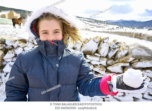 Blond kid girl playing with snow ball in winter